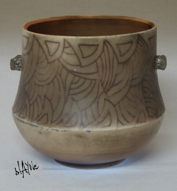 Slip inlay under a low temp. glaze, saggar fire.