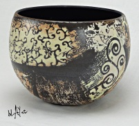 Black clay bowl with slip sprigs.