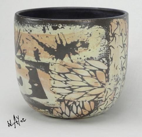 Black clay pot with ceramic slip sprigs.