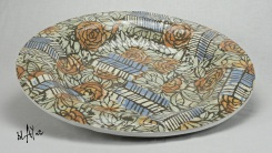 Stone ware slab that was slump molded and then decorated with stone ware slip sprigs.