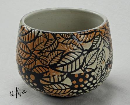 Stoneware cone 6 pot with slip sprigs , electric fire.